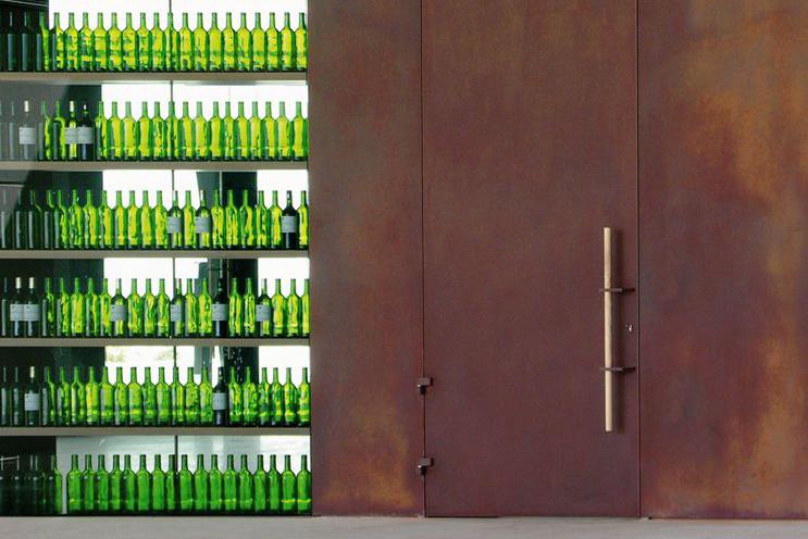Wandabwicklung mit Tür in Cortenstahl mit Stoßgriff aus Holz